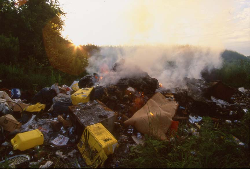 large pile burning farm trash with many plastics and herbicide jugs visible